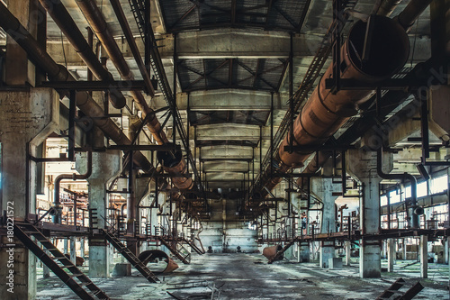 Spoed Foto op Canvas Oude verlaten gebouwen Abandoned Industrial workshop or hall of production for heavy industry factory . Huge steel pipes inside plant