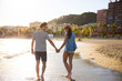 Happy couple walking in water holding hands