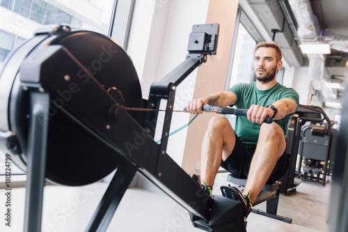 Fototapeta Active athlete man doing rowing workout obraz