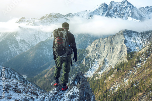 Fototapeta Man hiker with backpack on top of the mountain back, looking at the snow slope. Concept motivation and goal achievement obraz