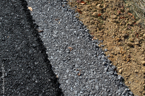 Fotografie, Obraz  Background of layers of a new roadway with asphalt, gravel, and dirt, horizontal