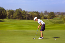Boy Golf Player Putting At Gre...