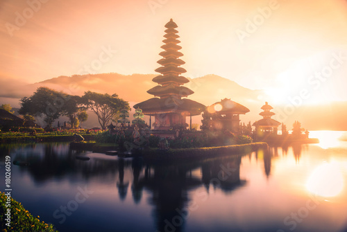 Pura Ulun Danu Bratan, Hindu temple on Bratan lake landscape with lens flare at sunrise in Bali, Indonesia.
