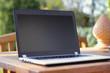 laptop on a wooden table in a garden environment
