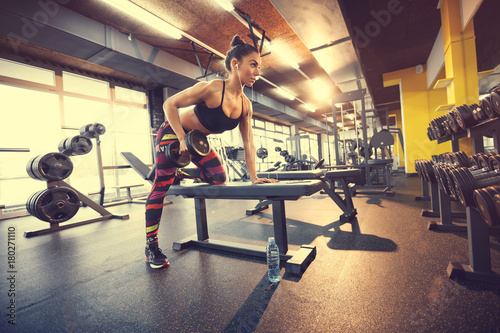 Poster Fitness Female exercising in gym with dumbbell