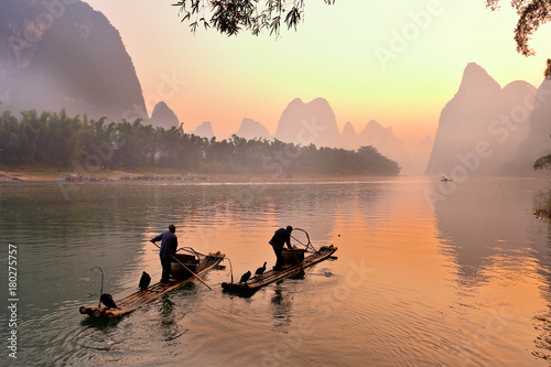 Photo Stands Guilin Silhouette of Two Fishing Men and His Cormorants on Li River at Sunrise, Guilin, China. The Li River or Lijiang is a river in Guangxi Zhuang Autonomous Region, China.