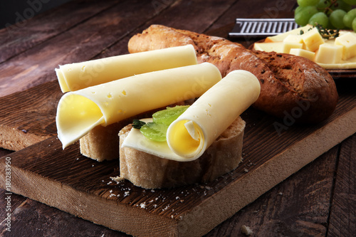 Cheese slices on bread or baghuette and grapes Fototapete