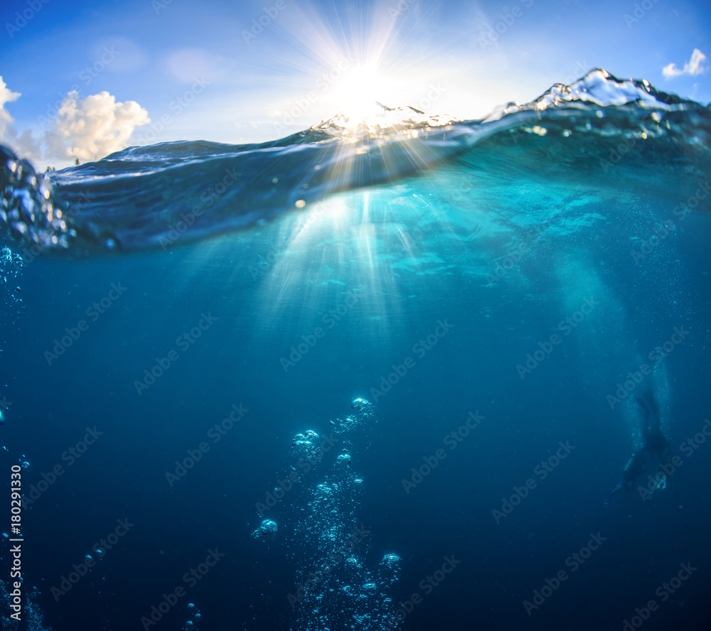 Fototapety, obrazy: Underwater scenery, deep blue water of the ocean, air bubbles, waterline splitting skyline, divers discovering sea