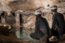 A Couple Of Speleologists Are Exploring A Cave, Punta Degli Stretti Cave, Tuscany, Italy