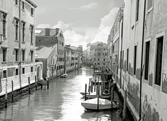 Fototapeta Black and white of small venetian canal and old brick walls with vintage traditional balconies. Venice, Italy