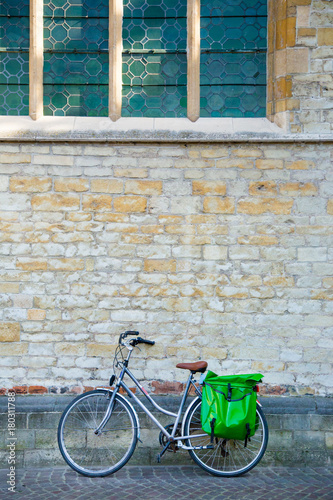 Deurstickers Fiets retro style bicycle parks leaning against old European church's stone wall