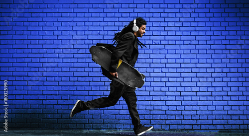 Stylish young dreadlocks hipster with headphones walking with a skate in hand near the blue brick wall on the street.