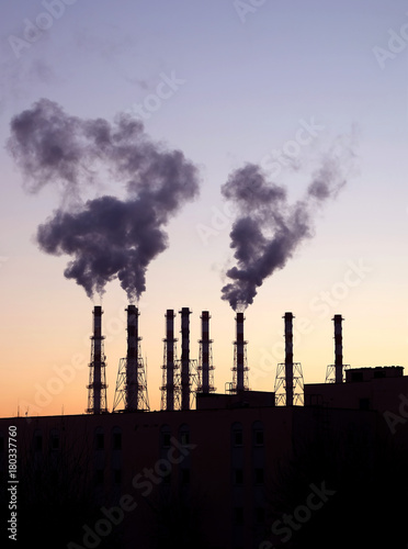 Fototapeta Industrial landscape with black silhouette of electric power station with many high smoke pipes in the evening after sunset over cloudless red and violet sky obraz na płótnie