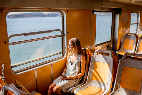 Fotomural Young woman traveling in the old ferry enjoying view on the sea from the window