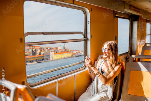 Photo Young woman traveling in the old ferry enjoying view on the Lisbon city from the