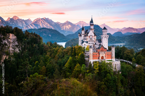 Spoed Foto op Canvas Kasteel The famous Neuschwanstein castle during sunrise, with colorful panorama of Alps in the background