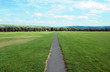 canvas print picture - long straight foortpath ina park with grass lawn and distant trees in halifax yorkshire