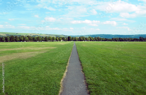 Fototapeta long straight foortpath ina park with grass lawn and distant trees in halifax yo