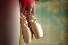 Young Ballet Dancer In The Backstage Waiting For The Show With Shoes In Her Hand. Blurred Scenography On The Background.