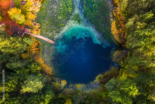 Fotografía  Aerial view of the karst lake named Goluboye Ozero (Blue Lake) surrounded by forest