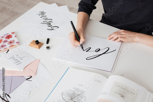 Fotografie, Tablou Photo of young woman hands writing beautiful notes on paper with open book on de