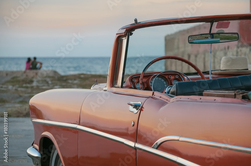 Classic American car in Havana in front of the sea. Cuba Canvas Print