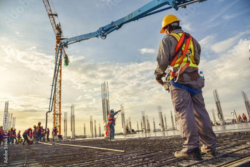 Fotografia  A construction worker control a pouring concrete pump on construction site and s