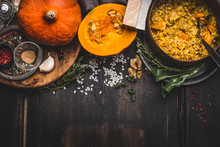 Cooking Pot Of Vegetarian Pumpkin Risotto And Spoon On Dark Rustic Kitchen Table Background With Cooking Ingredients, Top View, Border. Healthy Clean Seasonal Food And Eating Concept