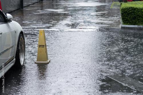 """Plakat zamknąć krople deszczu / zalanie wodą na ulicy i znak ostrzegawczy """"Uwaga mokrej podłodze"""" w samochodzie parkingowym."""