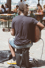 Street Musician Playing And Singing In Outdoor Cafe.