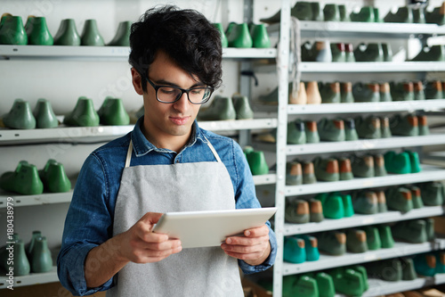 Modern shoe master with tablet taking online orders from