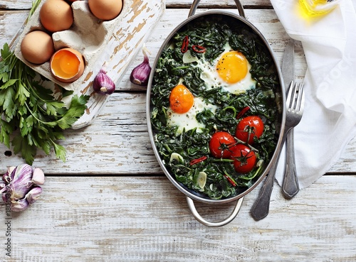 Eggs baked with spinach and tomatoes in serving pan overhead rustic wooden table. Overhead view.