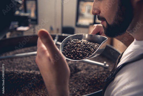 Poster de jardin Salle de cafe Serene bearded man enjoying burned beans aroma while holding them on spatula. Industry concept. Close up