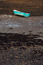 A Blue Rowing Boat Stranded On The Seabed With The Tide Out For The Day