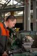 metalworking industry: factory man worker in uniform working on lathe machine in workshop