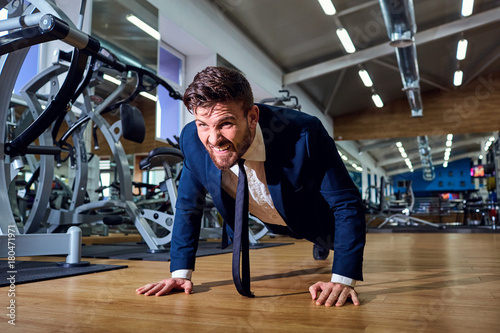 Foto op Plexiglas Fitness Businessman doing push-ups from the floor in the gym.