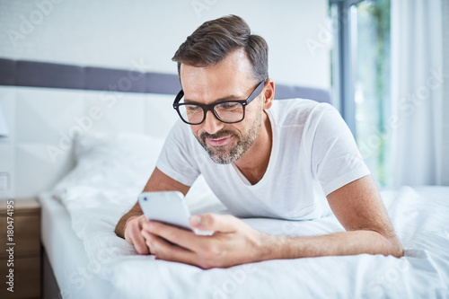 Smiling man using phone while lying in bed in the morning