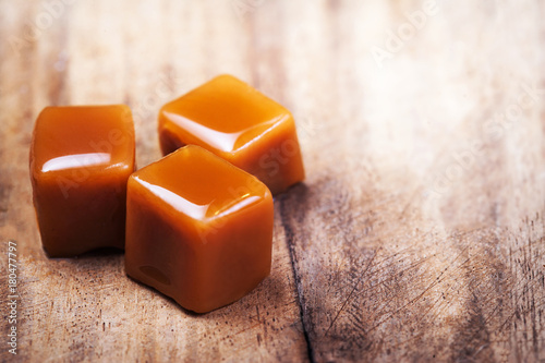 Homemade salted caramel pieces  on wooden  background. Golden Butterscotch toffee candy caramels with copyspace