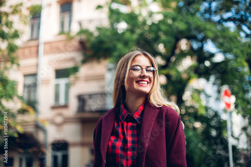 Fashion lifestyle portrait of young happy pretty woman laughing and having fun on the street at nice sunny summer day.