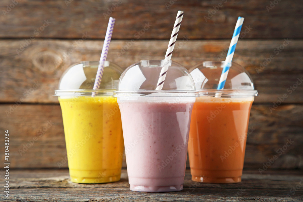 Fototapeta Sweet smoothie in plastic cups on wooden table