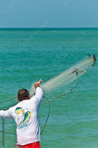 Fotografie, Obraz  Man seining offshore / Single Man seining off a tropical beach on the Gulf of Me