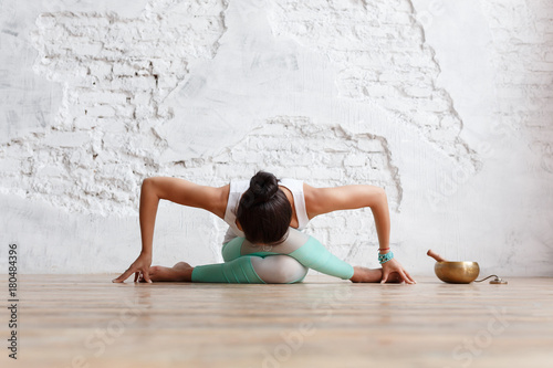 Fotografía  Young attractive woman practicing yoga in bright yoga class on wooden vintage fl