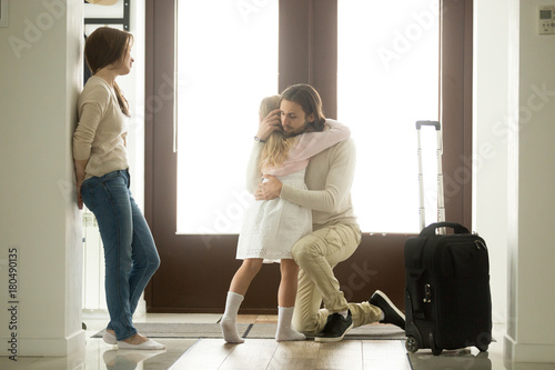 Foto Sad father hugging little daughter before leaving for long business trip, upset