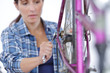Woman tightening nut on bicycle wheel