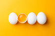 canvas print picture - White eggs and egg yolk on the yellow background. topview