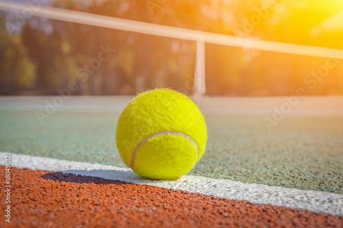 Plakat makro tenisowa piłka na linii na twardym boisku. rozmyte sieci w tle