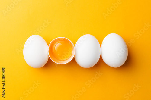Foto White eggs and egg yolk on the yellow background. topview