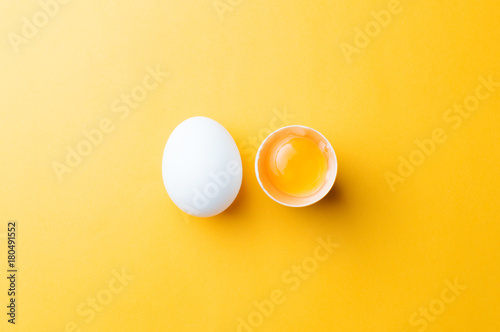 White egg and egg yolk on the yellow background. topview