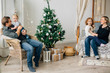 Young happy family of four near christmas tree. Mother with daughter on bed and father with son on armchair. Happy new year concept.