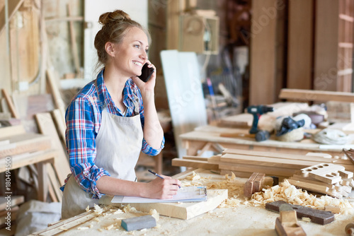 Portrait of modern young woman speaking by phone with client smiling and making notes in woodworking shop
